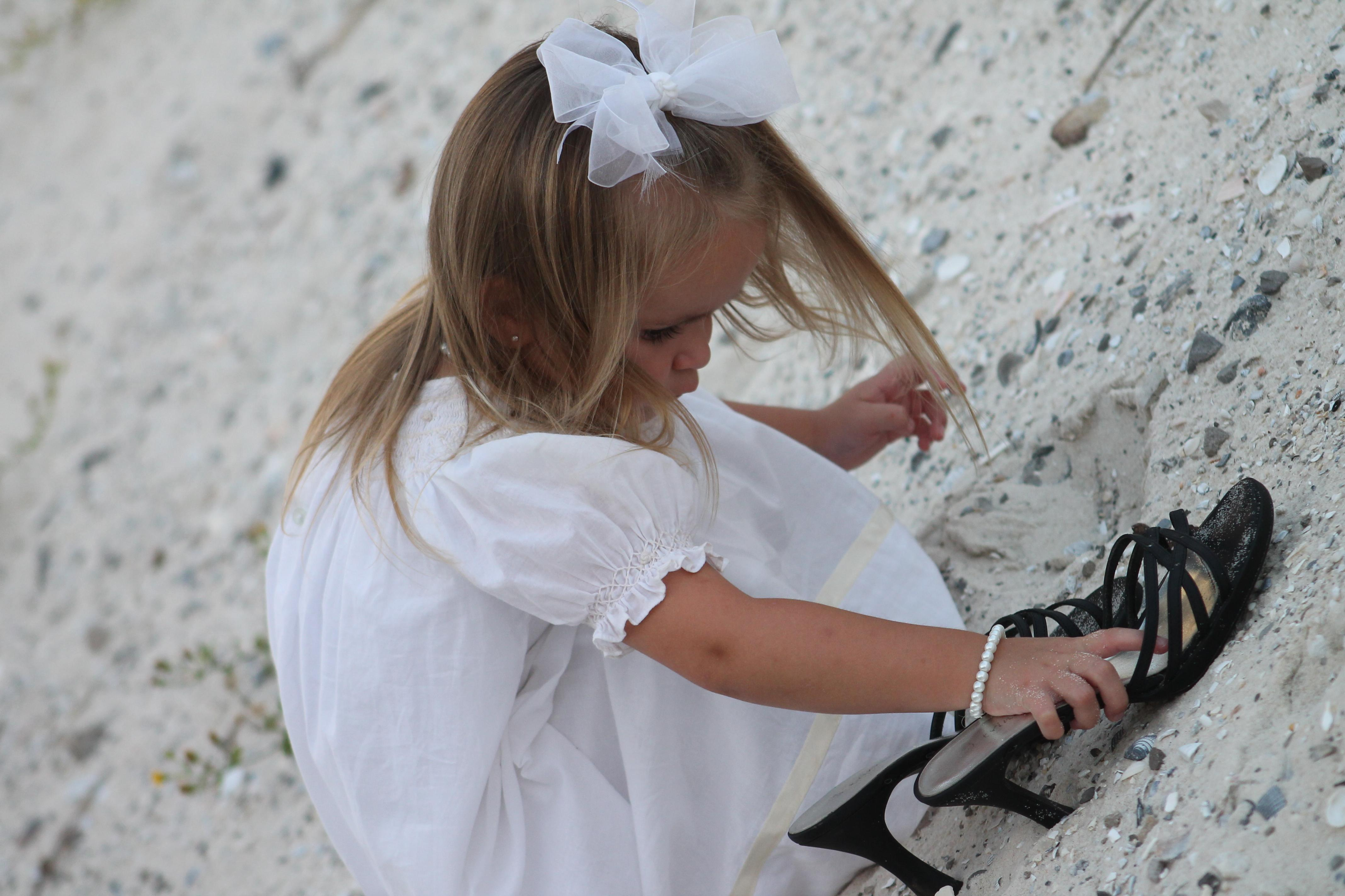 child at beach with mom's shoes