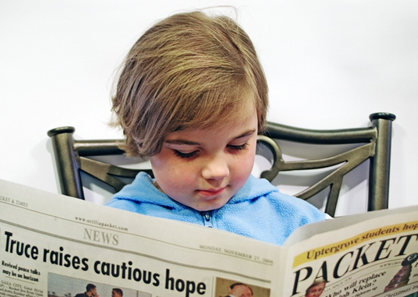 A young girl reading the current events in a newspaper; isolated on white background.